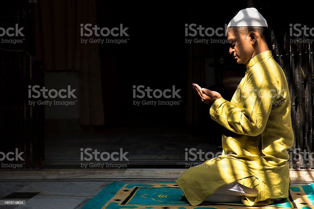 Young Muslim man praying, with folded hands stock photo