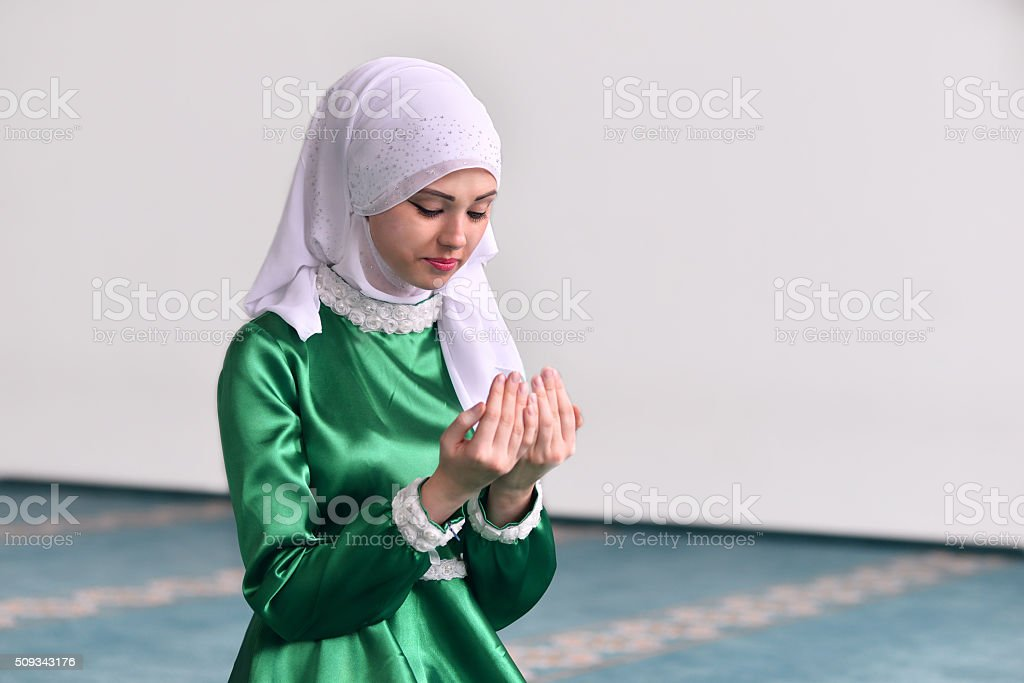 Young muslim woman praying in mosque stock photo