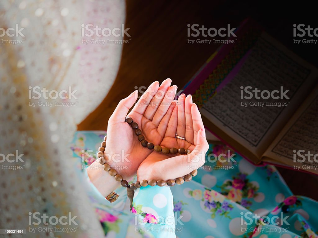 Young Muslim woman praying over beads stock photo