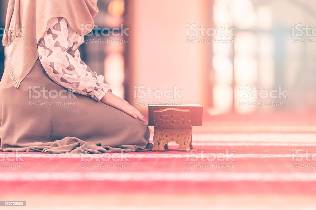 Young muslim woman reading koran in mosque stock photo