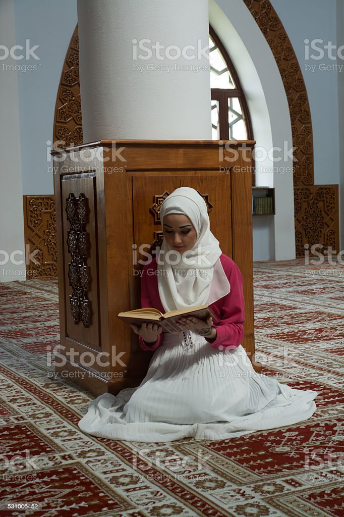 Young muslim woman reading Koran stock photo