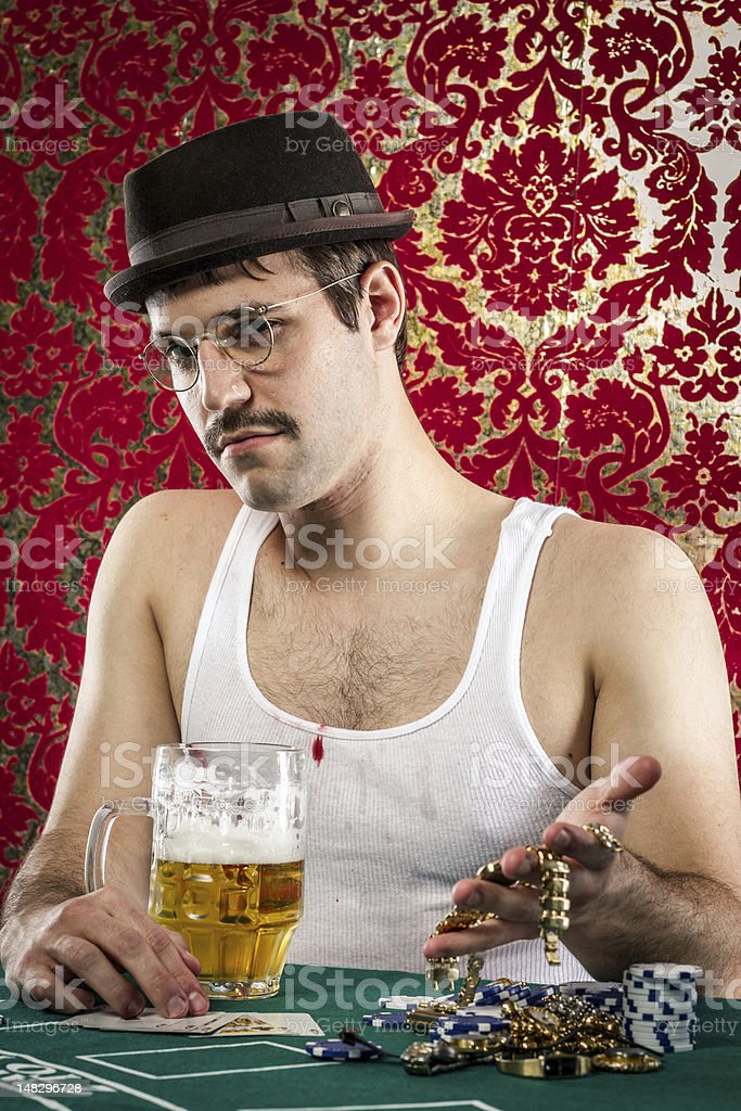 Young mustached eccentric man in vintage casino toasting beer stock photo