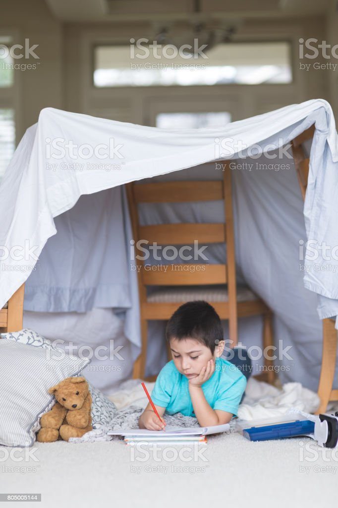 Young Native American boy draws in his sketchpad underneath his blanket fort in the living room stock photo