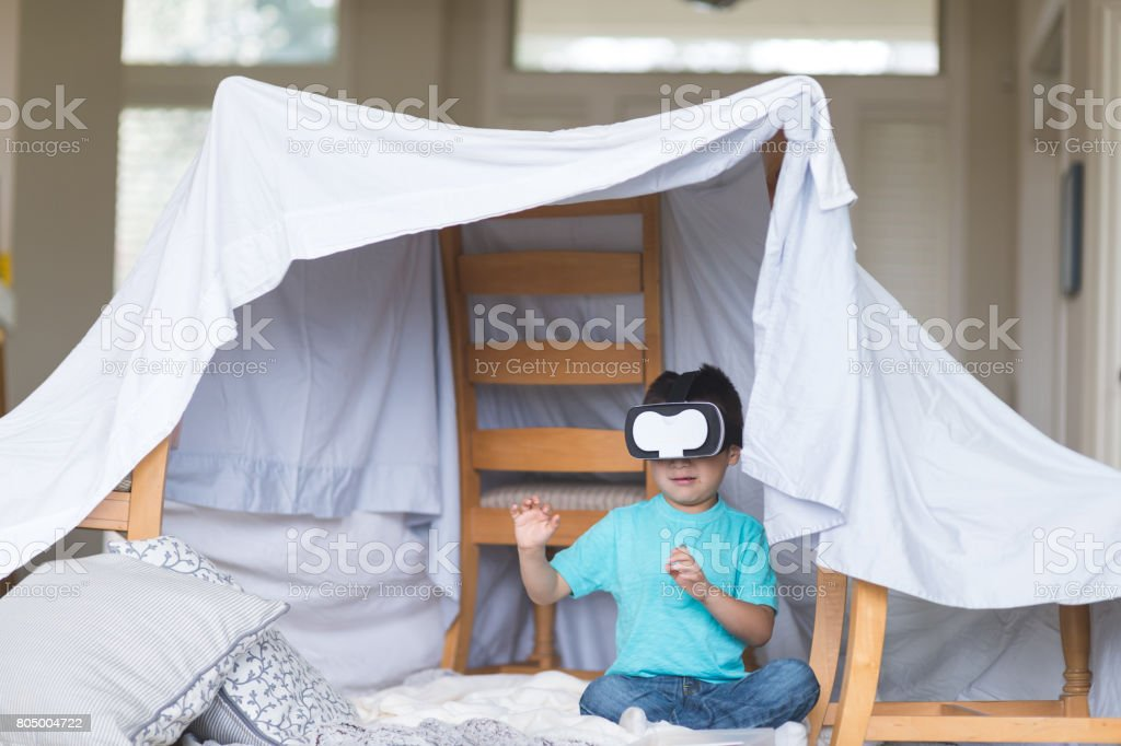Young Native American boy waves his arms around while wearing virtual reality glasses stock photo