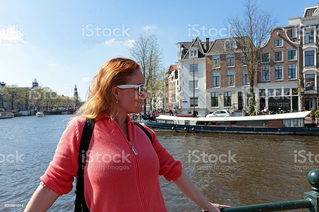 Young native dutch woman on a medieval bridge in Amsterdam stock photo