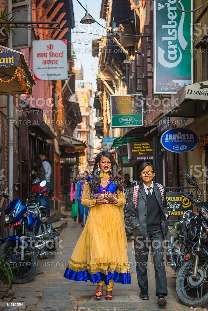 Young Nepalese women walking through narrow city alley Kathmandu Nepal stock photo