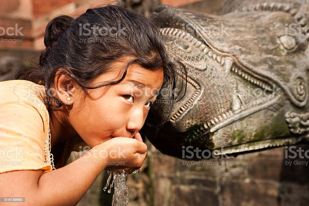 Young Nepali girl drinking from city fountain in Patan stock photo