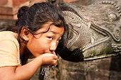 Young Nepali girl drinking from city fountain in Patan