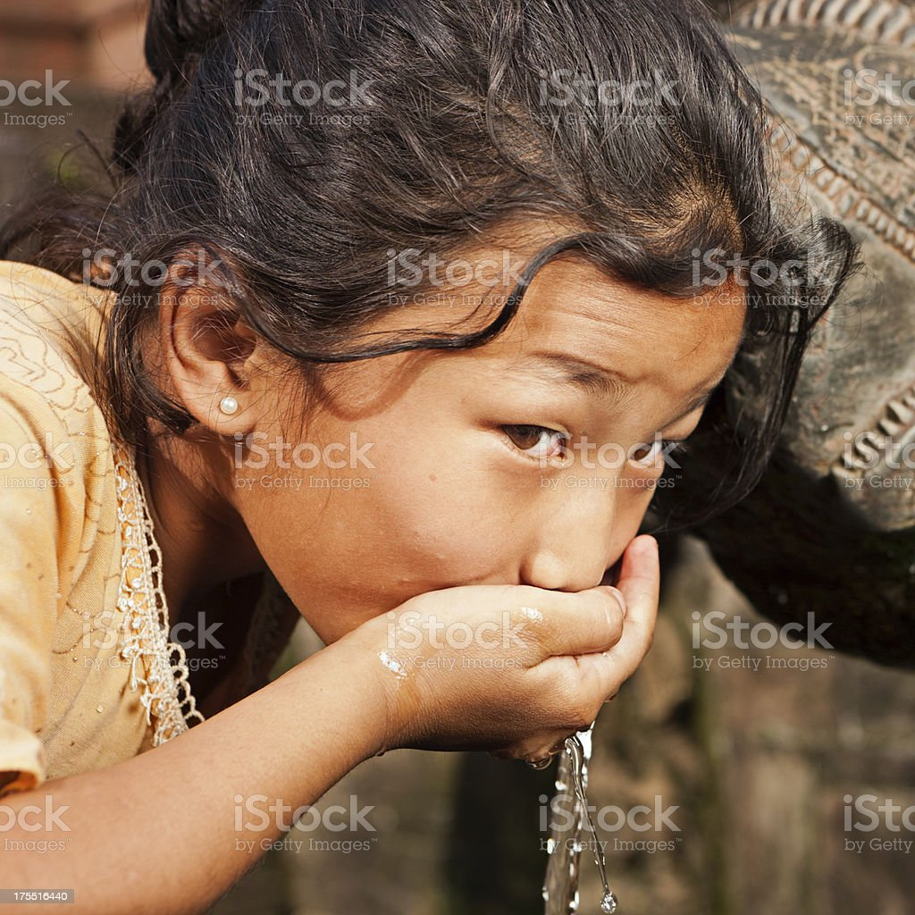 Young Nepali girl drinking from city fountain on Durbar Square stock photo