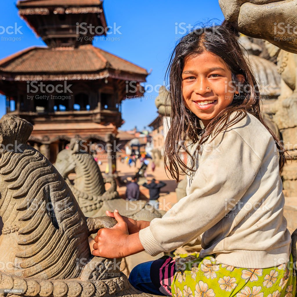 Young nepali girl having fun on Hindu  temple in Bhaktapur stock photo