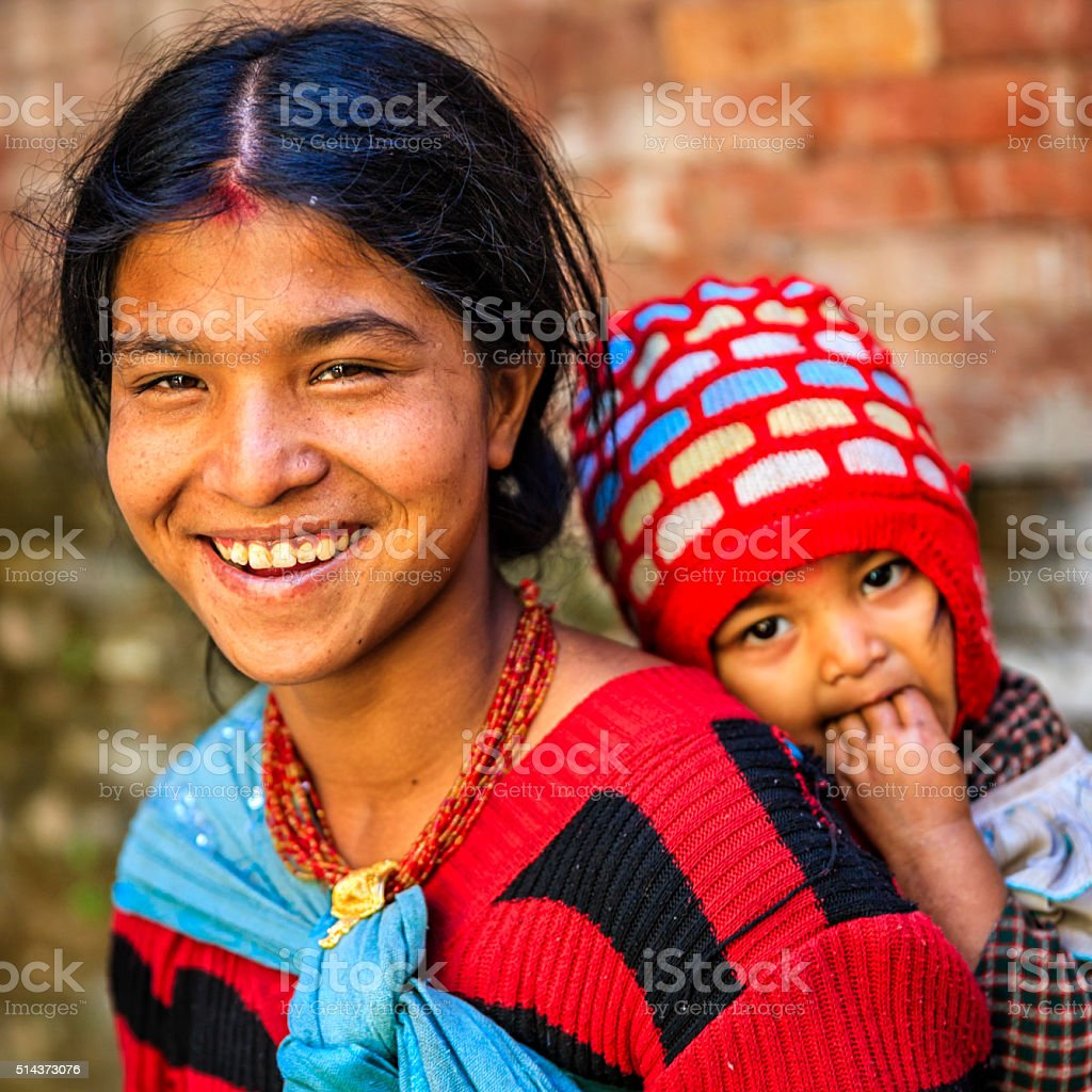Young Nepali mother carrying her baby, Kathmandu, Nepal stock photo