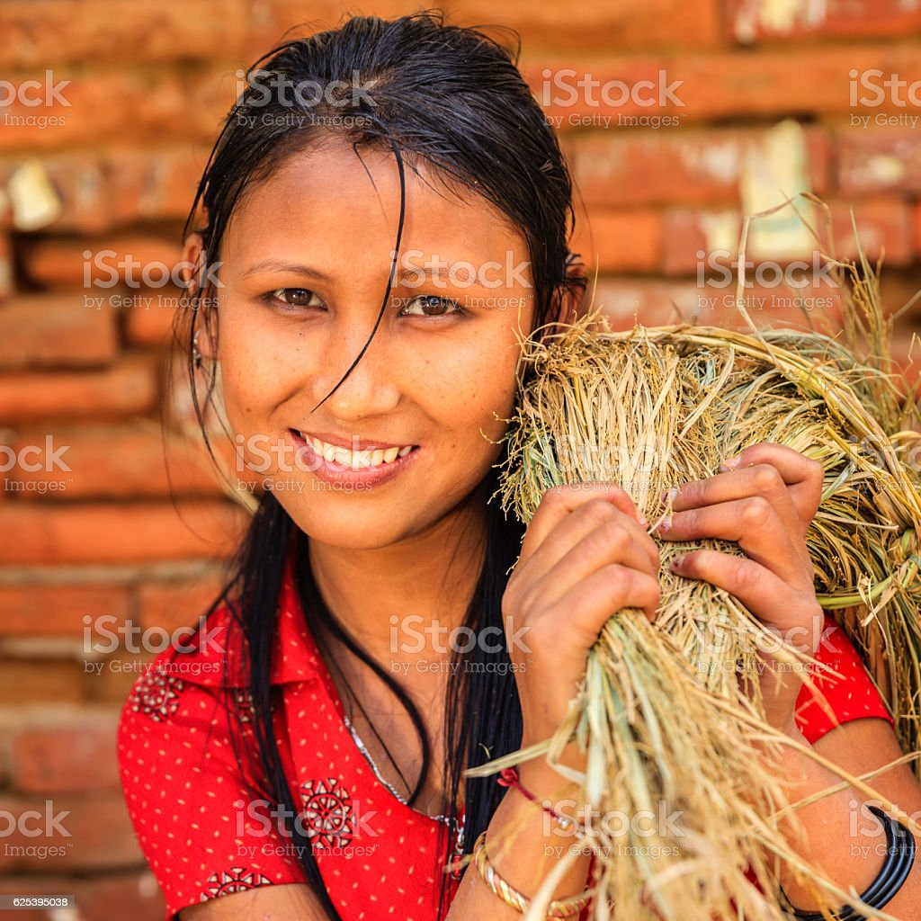 Young Nepali woman carrying a straw stock photo