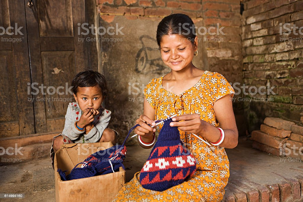 Young Nepali woman knitting wool hat in Bhaktapur stock photo