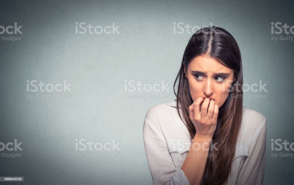Young nervous woman biting fingernails craving or anxious stock photo