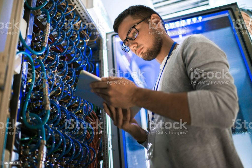 Low angle portrait of young man using digital tablet standing by...