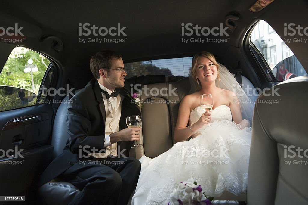 Young newlyweds drinking champagne in the limousine, horizontal stock photo