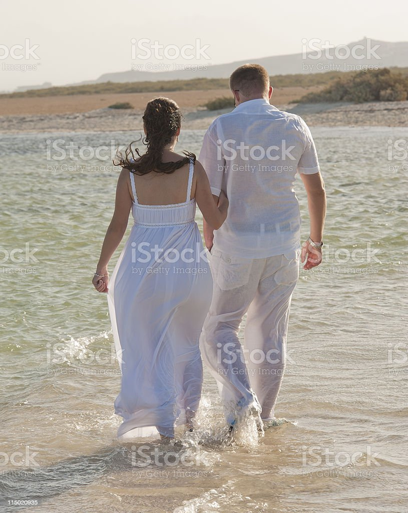 Young newlyweds walking on a tropical beach royalty-free stock photo
