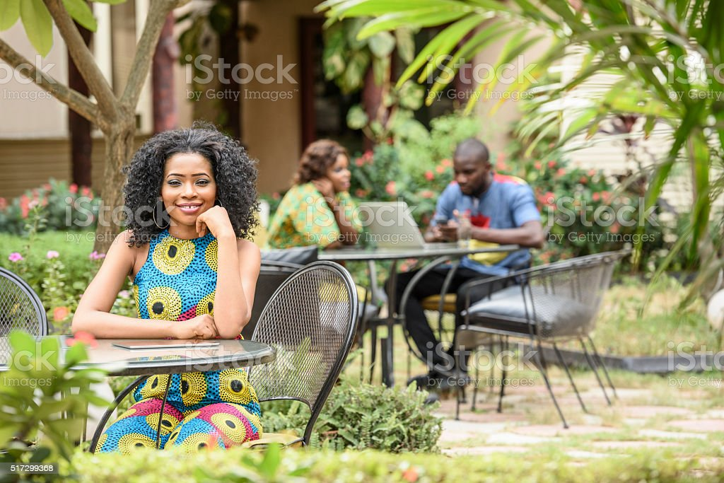Young Nigerian woman sitting in garden cafe, smiling stock photo