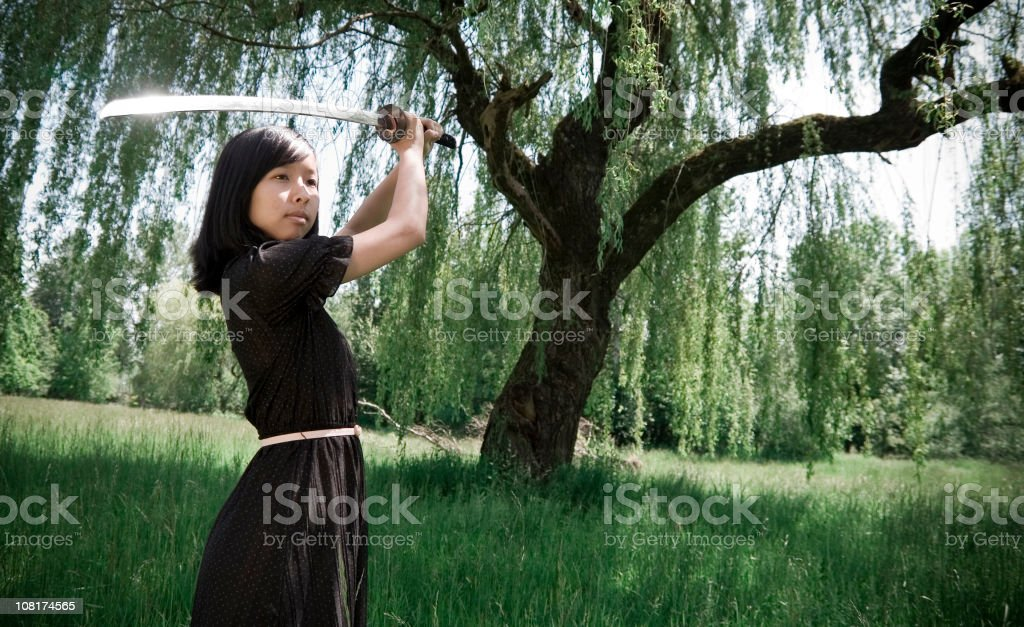 Young Ninja Girl In Summer Dress with Sword royalty-free stock photo