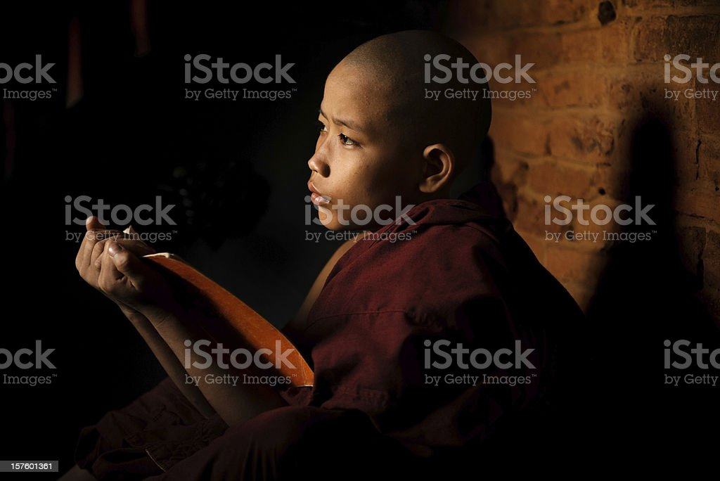 Young novice monk learning inside monastery stock photo