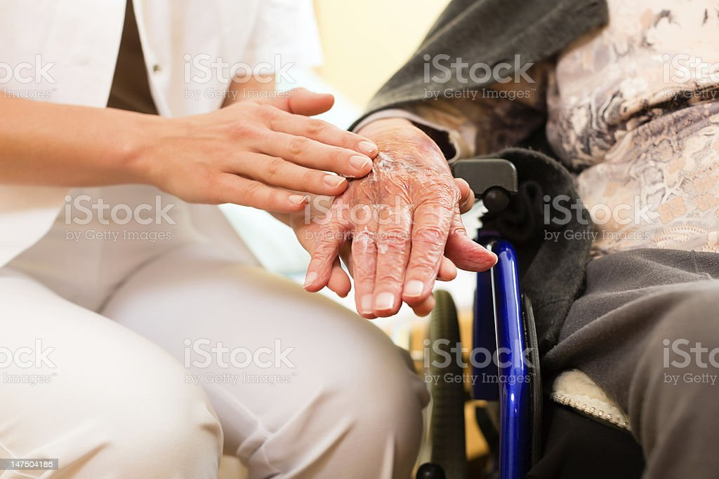 Young nurse and female senior in nursing home stock photo