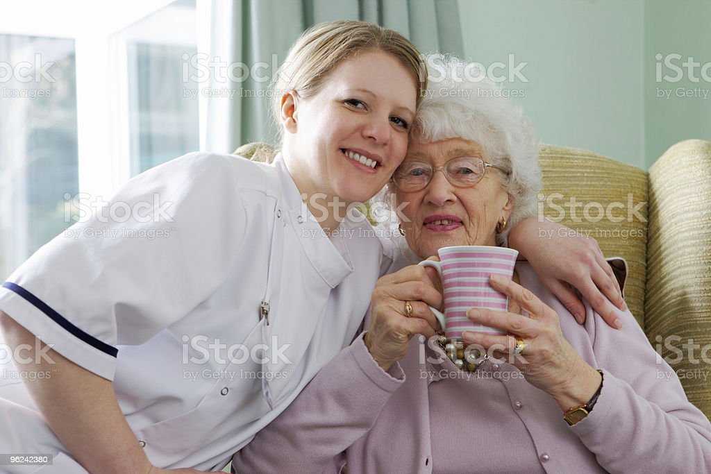 young Nurse and senior woman cuddling in a care home royalty-free stock photo