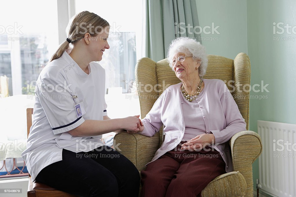 young nurse chatting with senior woman in a care home royalty-free stock photo