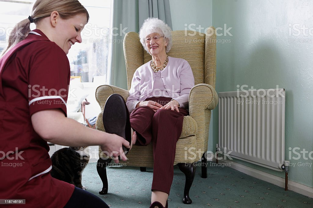young Nurse dressing senior woman in a care home stock photo