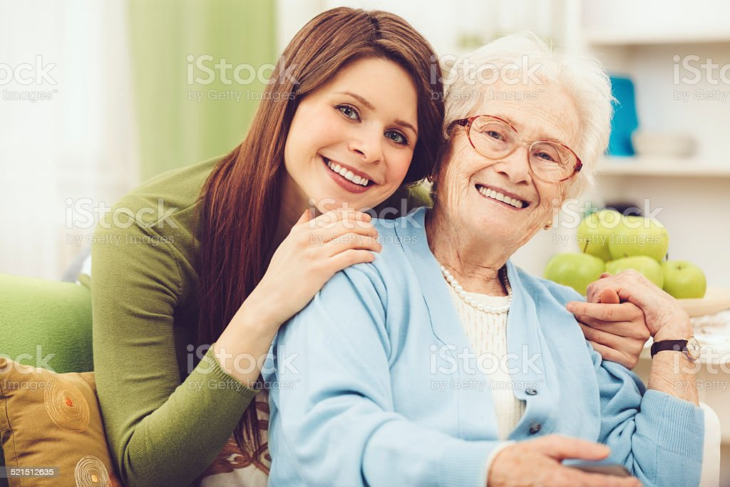 Young nurse embracing a happy senior woman stock photo