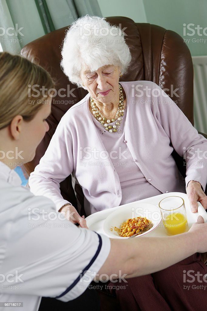 young nurse handing meal to elderly lady in care home stock photo
