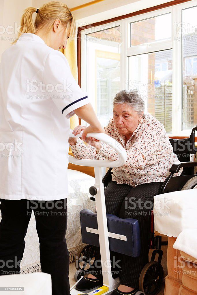 young nurse helping senior woman to stand with chair lift stock photo