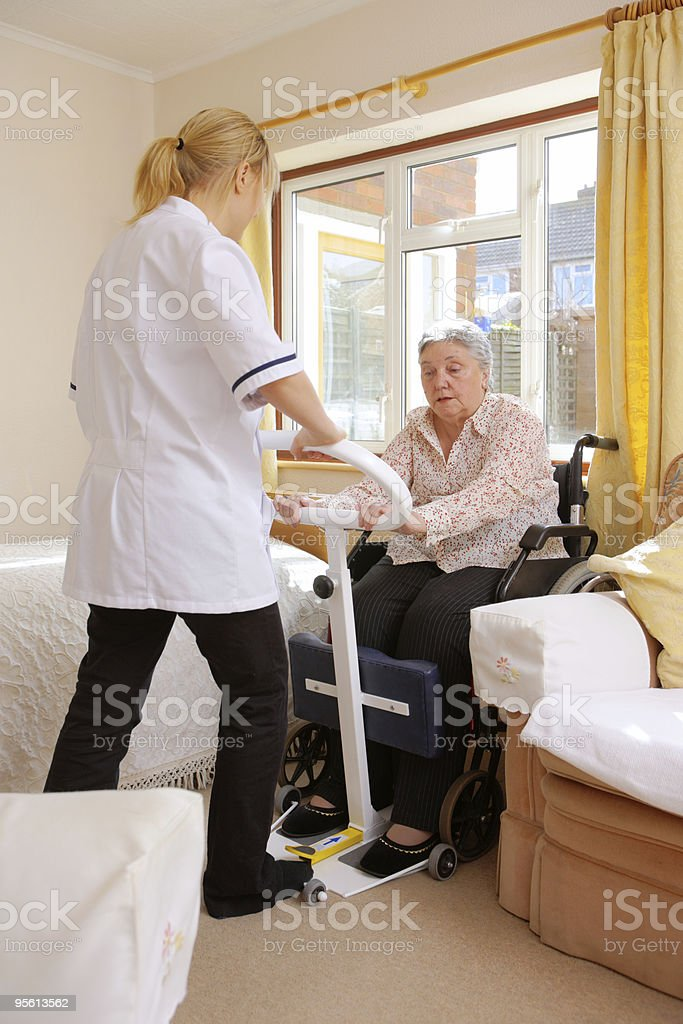 young nurse helps senior woman to stand in care home royalty-free stock photo