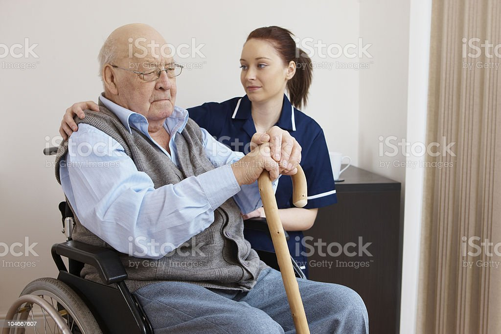 young nurse hugging senior man in wheelchair royalty-free stock photo