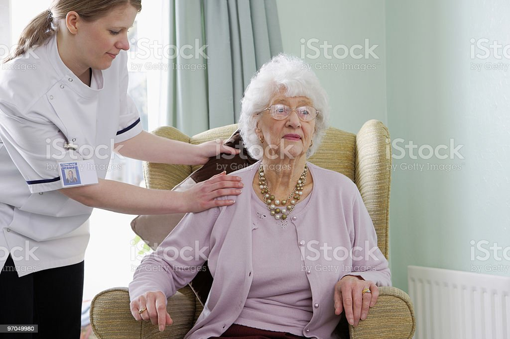 young nurse making senior woman more comfortable in chair royalty-free stock photo