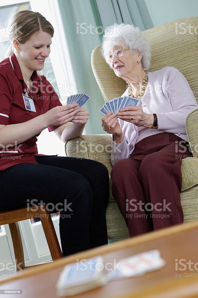 young Nurse playing cards with senior woman in care home stock photo