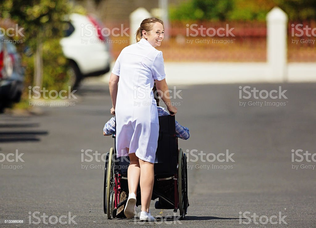 Young nurse pushing patient in wheelchair looks round, smiling stock photo