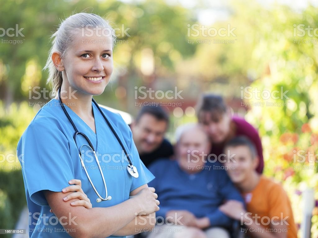Young nurse smiling with happy family in the background  stock photo