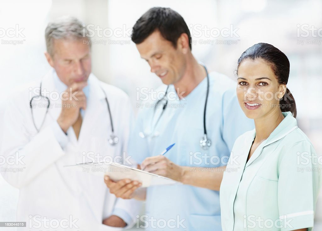 Young nurse with two blurred doctors discussing in background royalty-free stock photo