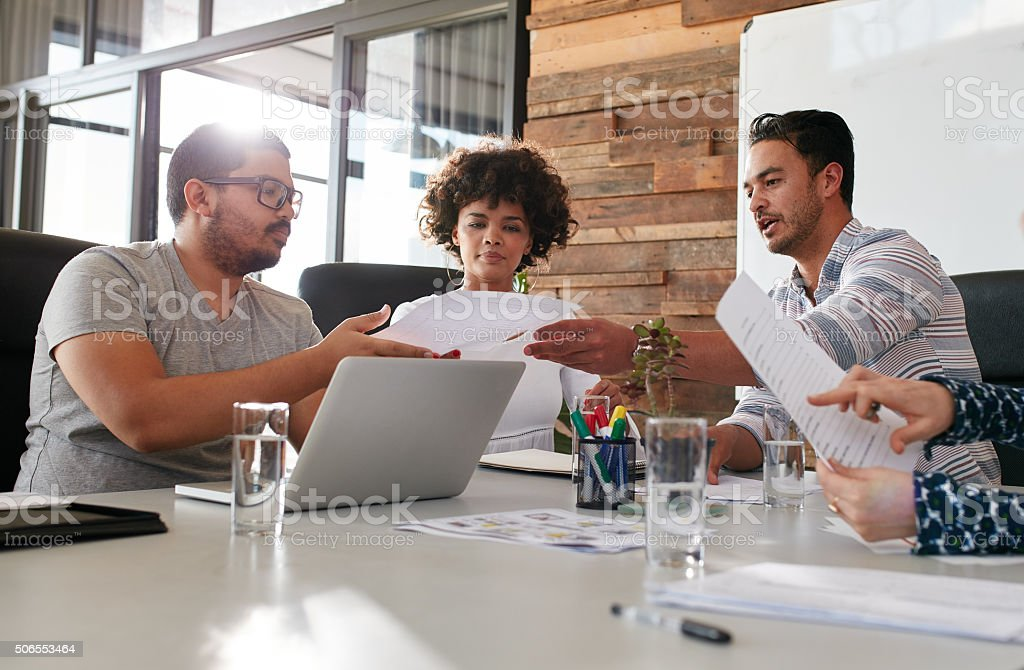 Young office workers discussing work in a boardroom stock photo