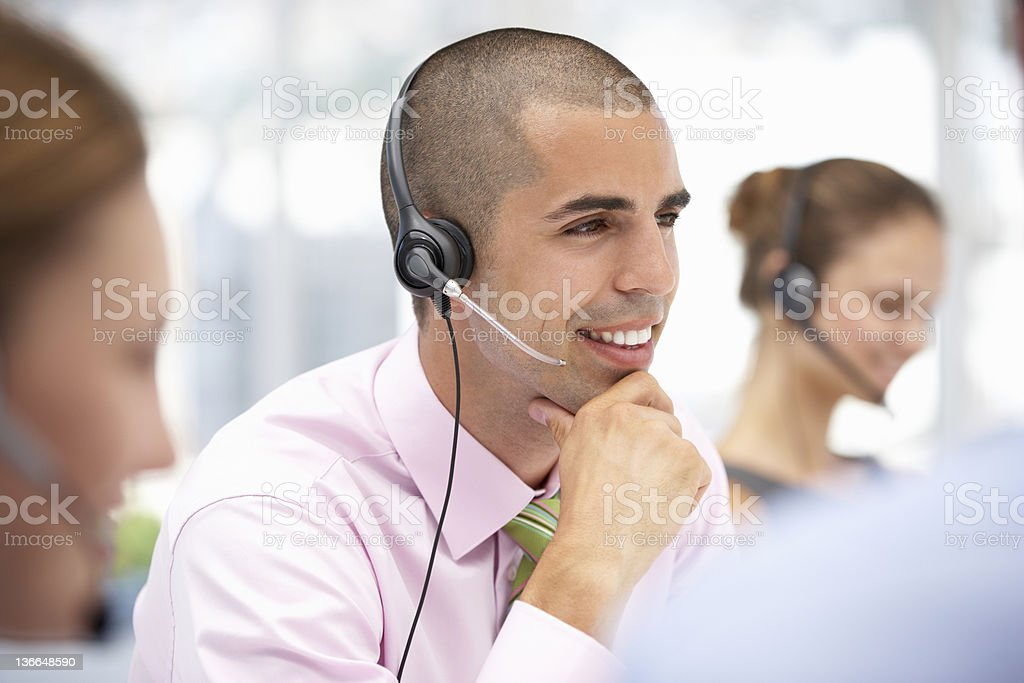 Young operator talking to customers through headset stock photo