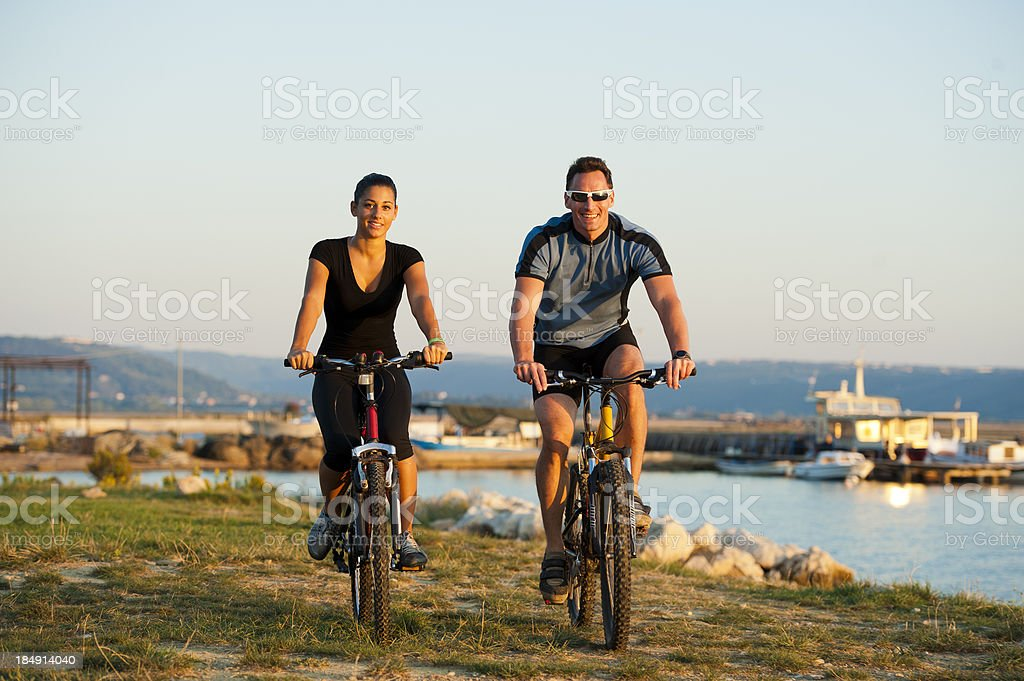 Young pair cycling by the sea royalty-free stock photo
