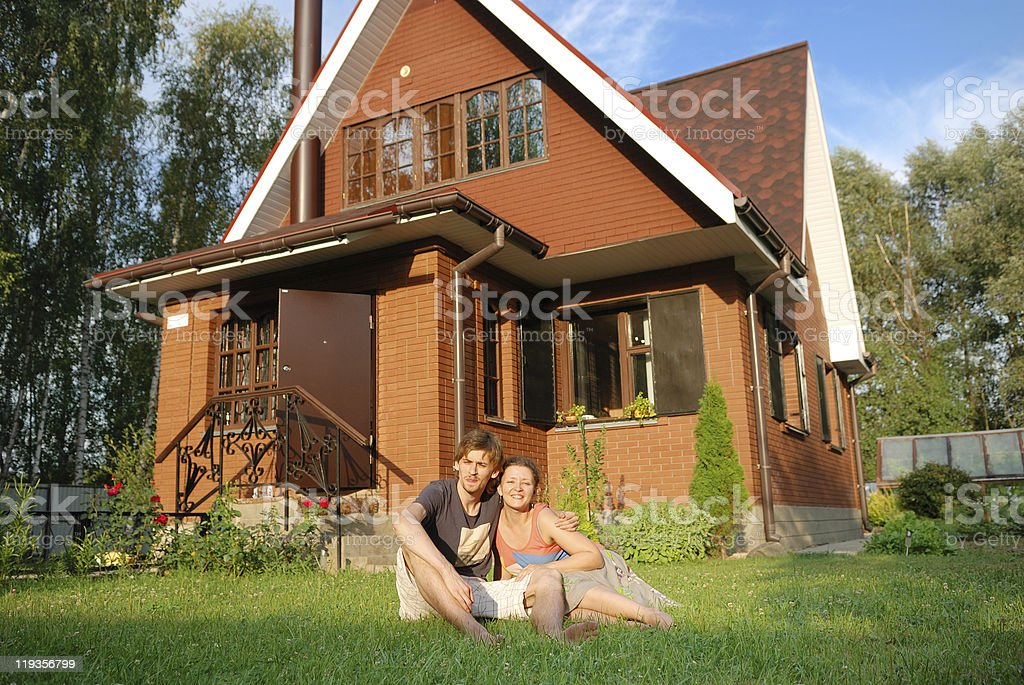 young pair sitting near new house royalty-free stock photo