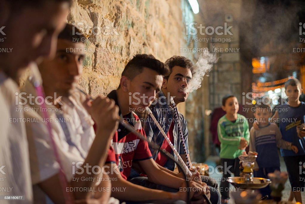 Young Palestinian adults smoking in Jerusalem's Muslim Quarter stock photo