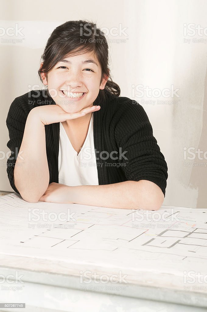 Young Pan-Asian Woman with Architectural Plans in Unfinished Room royalty-free stock photo