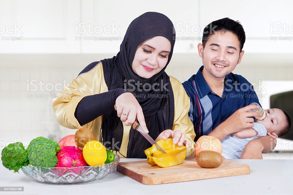 Young parents and son cooking with fruits stock photo