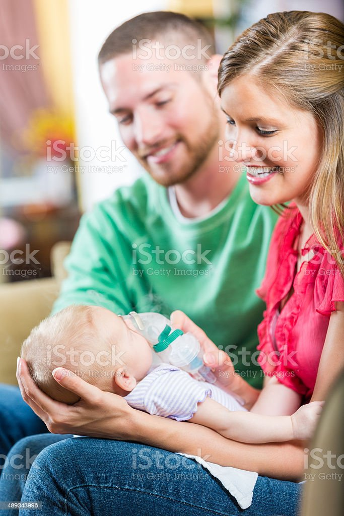 Young parents holding newborn baby girl at home stock photo