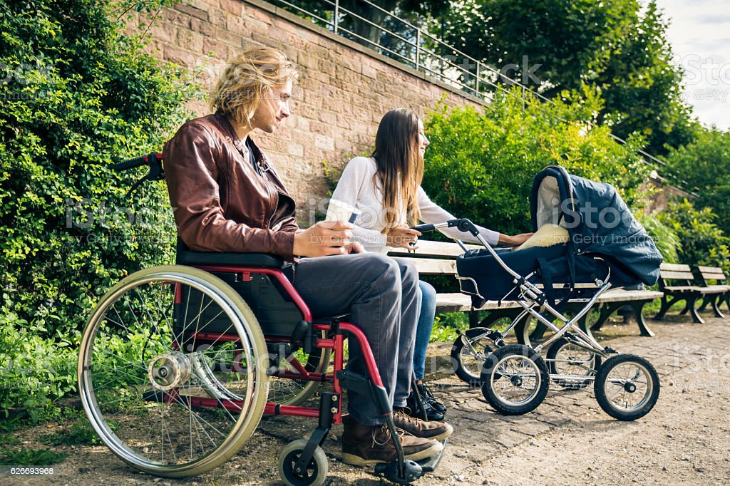 Young parents in wheelchair with baby stroller in the park stock photo
