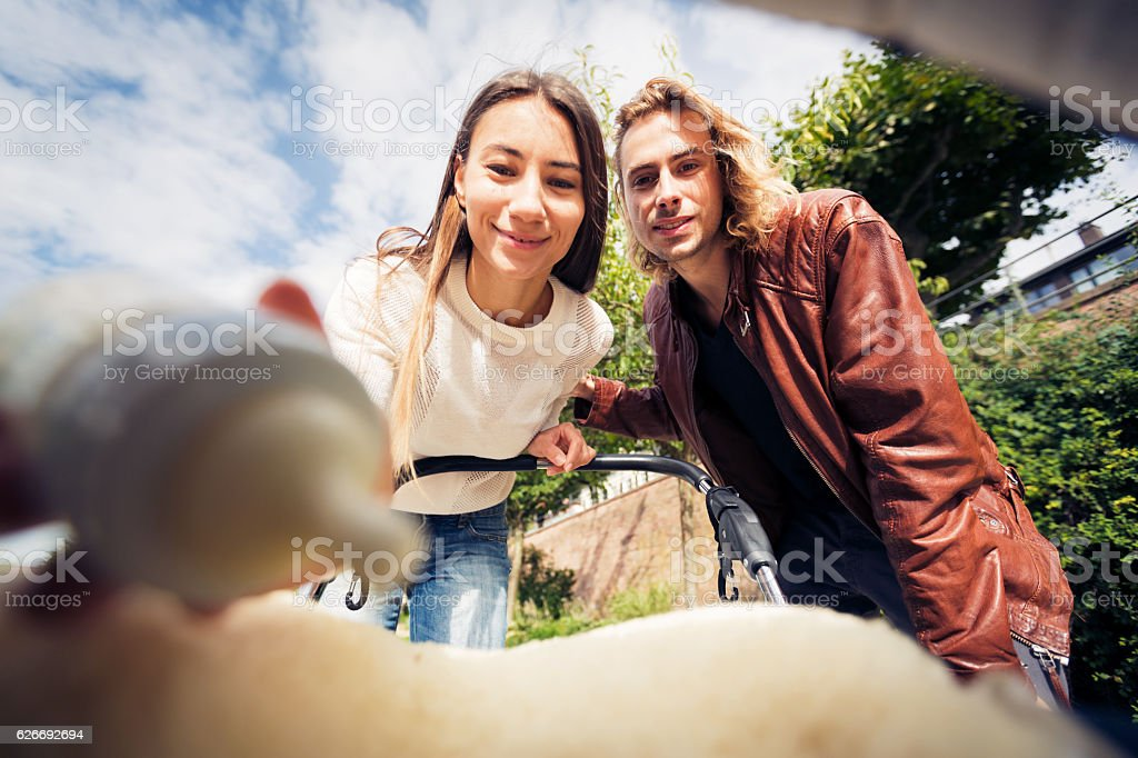 Young parents looking at their baby in a stroller stock photo