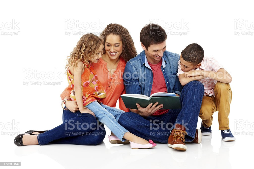 Young parents reading a story book to their kids royalty-free stock photo