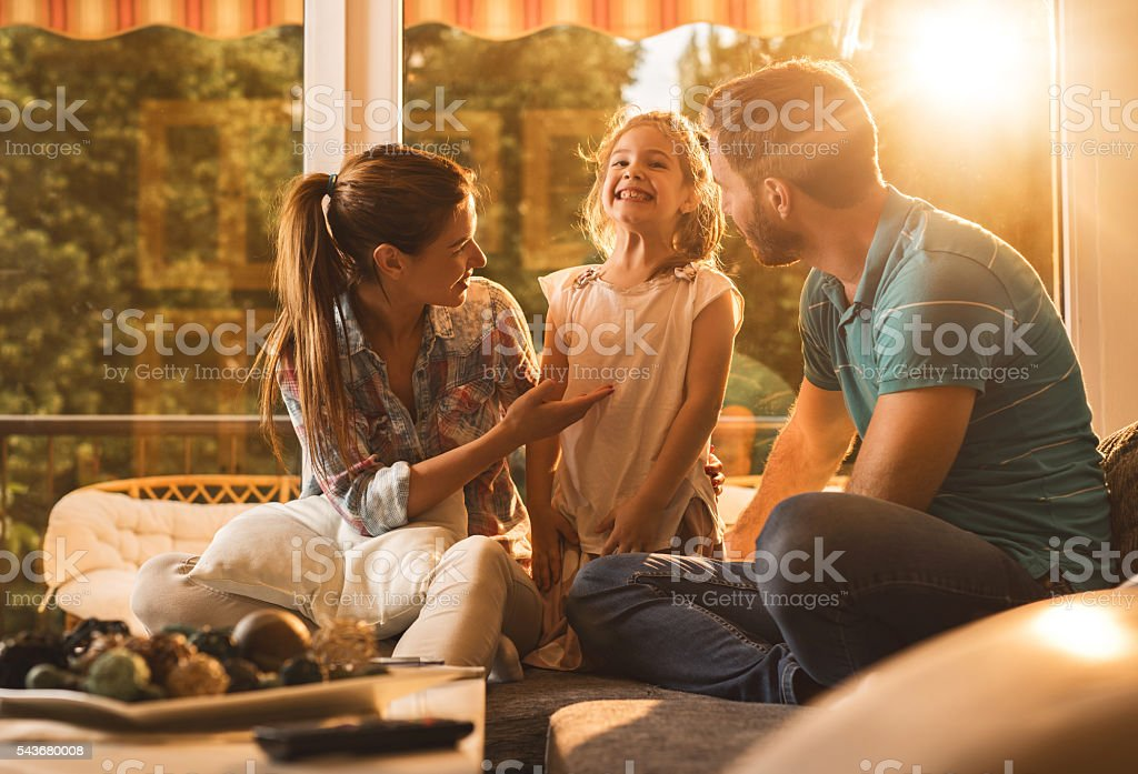 Young parents talking to their funny little daughter at home. stock photo